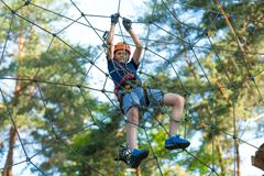 stock image of  child in forest adventure park. kid in orange helmet and blue t shirt climbs on high rope trail. agility skills