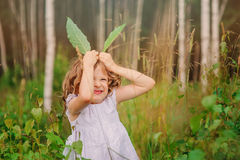 stock image of  child girl playing with leaves in summer forest with birch trees. nature exploration with kids.