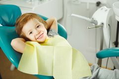 stock image of  child in good mood sitting on chair and without fear waiting dentist. young boy is going to treat teeth. caries