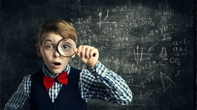 stock image of  child magnifying glass, amazed school kid, student boy with magn