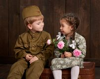 stock image of  children boy are dressed as soldier in retro military uniforms and girl in pink dress sitting on old suitcase, dark wood backgroun