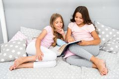 stock image of  children read book in bed. girls best friends read fairy tale before sleep. best books for kids. reading before bed can