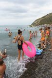 stock image of  children swim in the black sea near the shore on a cloudy summer day. bad weather does not interfere with people`s rest