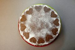 stock image of  chocolate biscuit cake with cocoa cream with small hearts from powdered sugar. dessert. valentine`s day concept. flat lay top vie
