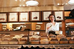 stock image of  chocolate store. female seller in confectionery shop.