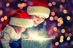 stock image of  christmas magic gift box and a happy family mother and baby