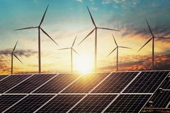 stock image of  clean energy power concept solar panel with wind turbine and sunset