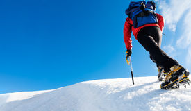 stock image of  a climber reaches the top of a snowy mountain. concept: courage, success, perseverance, effort, self-realization.