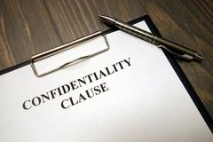 stock image of  clipboard with confidentiality clause and pen on desk
