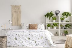 stock image of  close to nature bright bedroom interior with many green plants beside a big bed. woven tapestry above the bed. real photo.