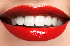 stock image of  close up beauty portrait view of a young woman natural smile with red lips. classic beauty detail. red lipstick and white teeth