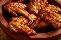 stock image of  close up of delicious grilled chicken wings in wooden bowl on wooden table.