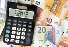 stock image of  german word rente pension on display of pocket calculator against paper money
