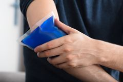 stock image of  person applying ice gel pack on an injured elbow