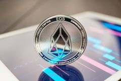 stock image of  close-up photo of eos cryptocurrency physical coin on the tablet computer showing stock market charts. trading eos cryptocoin