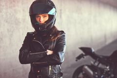 stock image of  close-up portrait of a biker girl with her arms crossed next to her superbike inside the bridge.