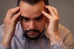 stock image of  closeup portrait of a stressed middle-aged man in grey shirt sitting indoor with sad face and thinking holding head in hands