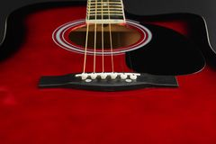 stock image of  closeup of a six stringed red acoustic guitar, from bridge side. music entertainment background