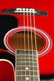 stock image of  closeup of a six stringed red acoustic guitar, from fingerboard side. music entertainment background