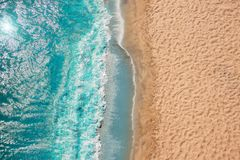 stock image of  coastline beach ocean waves with foam on the sand. top view from drone.