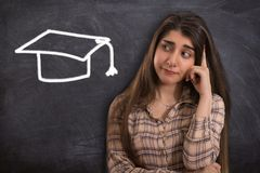 stock image of  college girl thinking with graduation cap