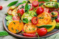 stock image of  colored tomato salad with onion and basil. vegan food.