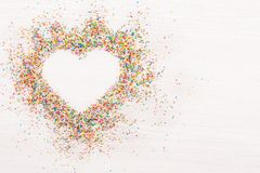 stock image of  colorful sprinkles sprinkled in shape of heart flatlay on white and grey wooden background