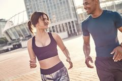 stock image of  common hobbies. young and happy multiracial couple running across sunny streets in the morning.