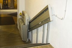 stock image of  a compact assistive support stair lift on a short flight of stairs in a public building in northern ireland