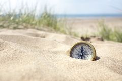stock image of  compass on the beach with sand and sea