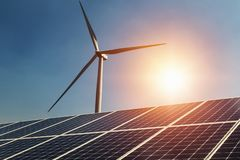 stock image of  concept clean energy power in nature. solar panel and wind turbine with sunlight blue sky background