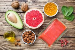 stock image of  concept healthy food antioxidant products: fish and avocado, nuts and fish oil, grapefruit on wooden background