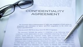 stock image of  confidentiality agreement, lying on table, pen and eyeglasses on document