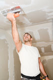 stock image of  construction industry worker with tools plastering walls and renovating house in construction site