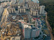 stock image of  construction site with building cranes and other equipment, industrial built or estate development modern buildings, aerial view