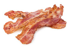 stock image of  cooked bacon rashers close-up isolated on a white background.