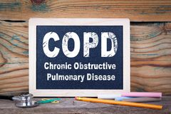 stock image of  copd, chronic obstructive pulmonary disease. chalkboard on a wooden background