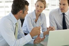 stock image of  corporate business teamwork - businessmen and woman working on laptop