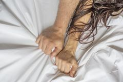 stock image of  couple hands pulling white sheets in ecstasy, orgasm. concept of passion. oorgasm. erotic moments. intimate concept. sex
