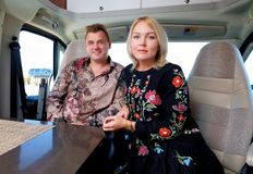 stock image of  couple sitting inside of recreational vehicle looking at camera