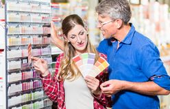 stock image of  couple choosing color of paint in hardware store