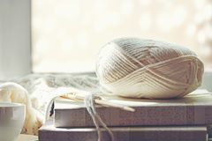 stock image of  cozy winter home with warm knitted sweaters and ball of yarn near windowsill, home hobbies,