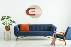 stock image of  creative geometric art on a white wall above an elegant blue sofa in a mid-century modern style living room interior. real photo.