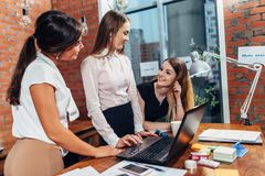 stock image of  creative team working on new project together looking and listening to their partner standing around desk using portable
