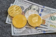 stock image of  crypto currency. coins bitcoin (btc)and ethereum (eth) ,on background of banknotes one hundred dollars .blockchain.intarnational c