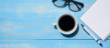stock image of  cup of black coffee with office supplies; pen, notebook and eyes glasses on blue wooden table background