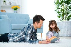 stock image of  cute little girl listening to dad reading fairy tale lying on warm floor together, caring father holding book , family hobbies