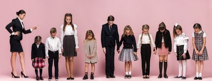stock image of  cute stylish children on pink studio background. the beautiful teen girls and boy standing together