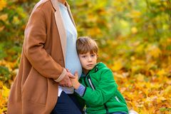 stock image of  cute sweet caucasian child listening to his pregnant mother`s belly expecting baby shaking in the tummy. expectations