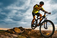 stock image of  cyclist riding the mountain bike on rocky trail at sunset. extreme sport and enduro biking concept.